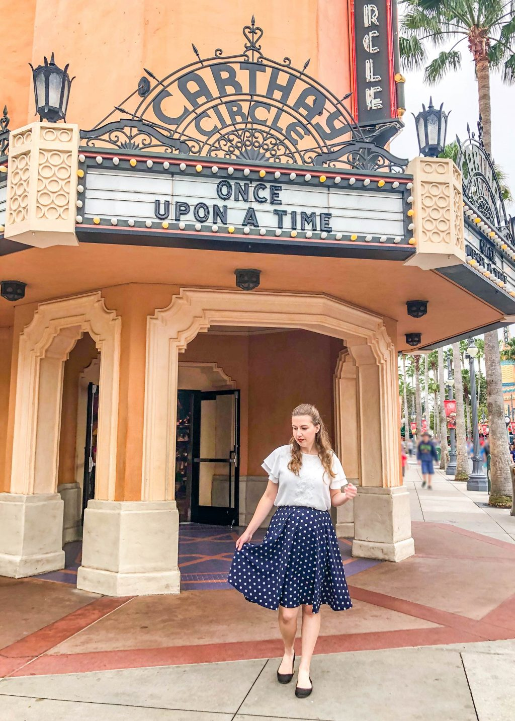 """Girl with white shirt and blue skirt stands out front of Carthay Circle. A large letter board on the building reads """"Once Upon a Time""""."""