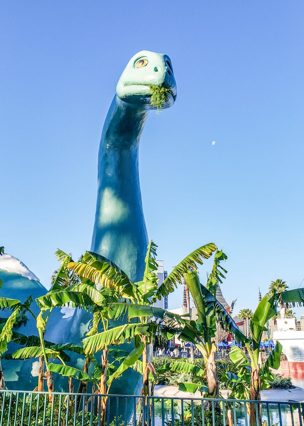 A large green dinosaur rises among the palm trees, while eating some kind of greenery