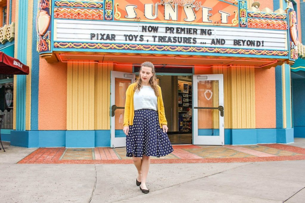 Girl with navy blue skirt, white top, and yellow jacket stands in front of a lare storefront with yellow and orange walls, blue lining, and a retro movie theater letter sign.
