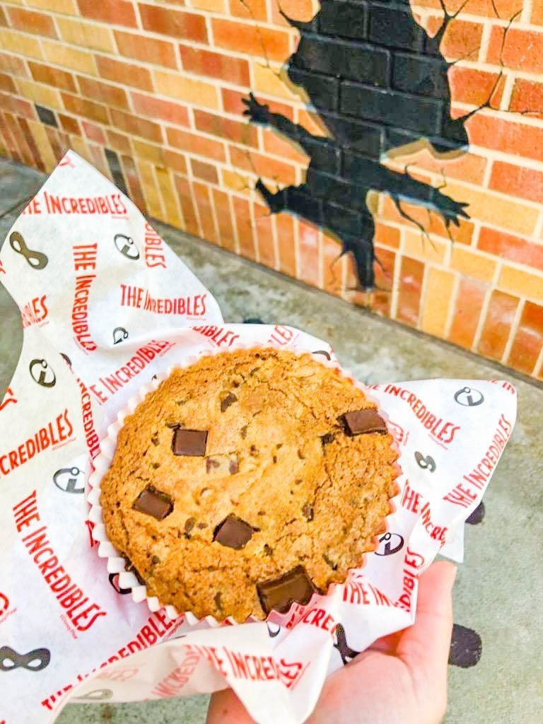 A large cookie in front of a brick wall with the outline of Jack-Jack on the wall.