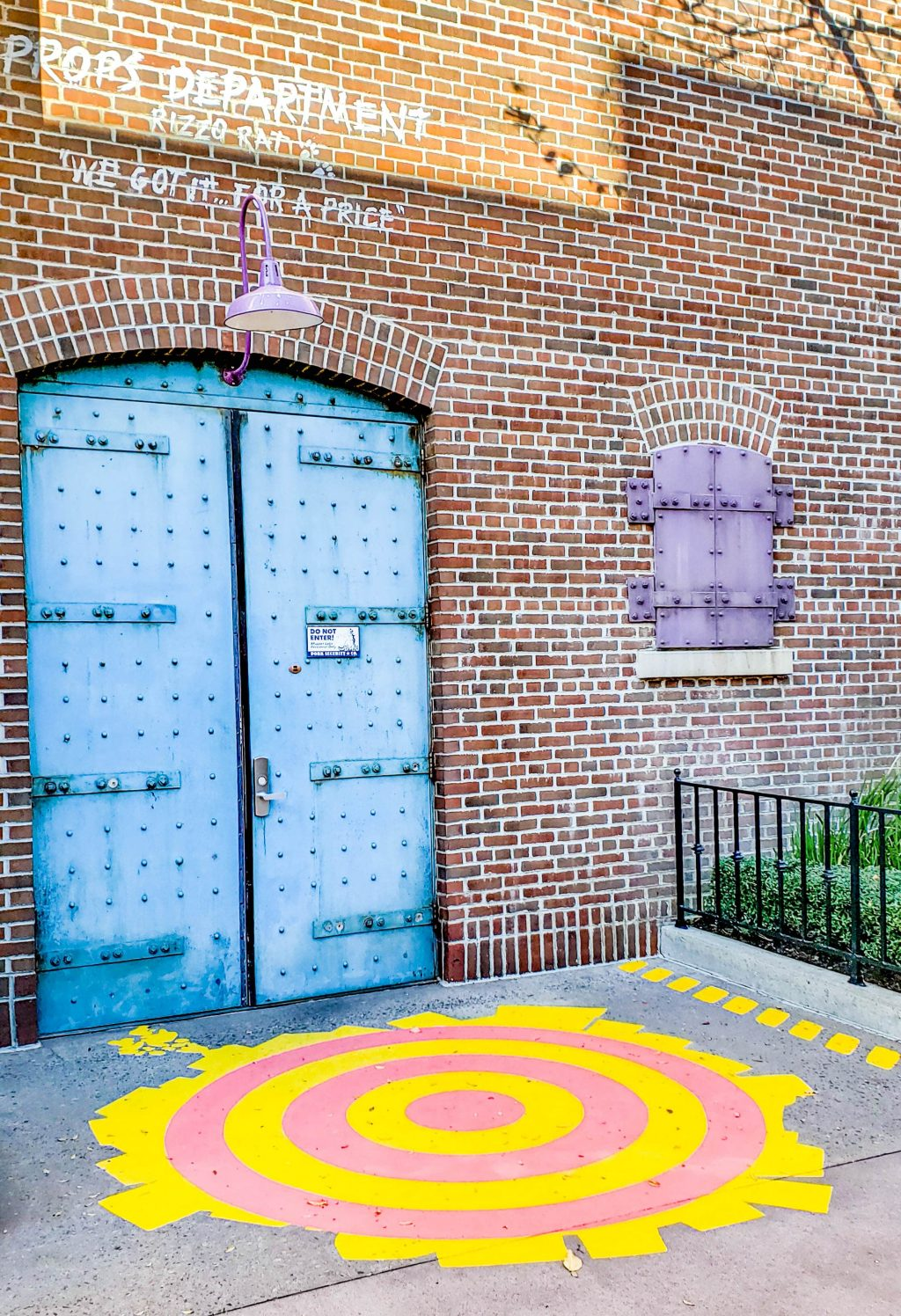 A bright blue door on a brick wall. The ground has a red target with a giant yellow paint splotch.