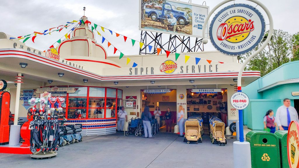 The facade of the stroller rental at Hollywood Studios looks like a retro gas station, including red gas pumps and small flags on top of the building.