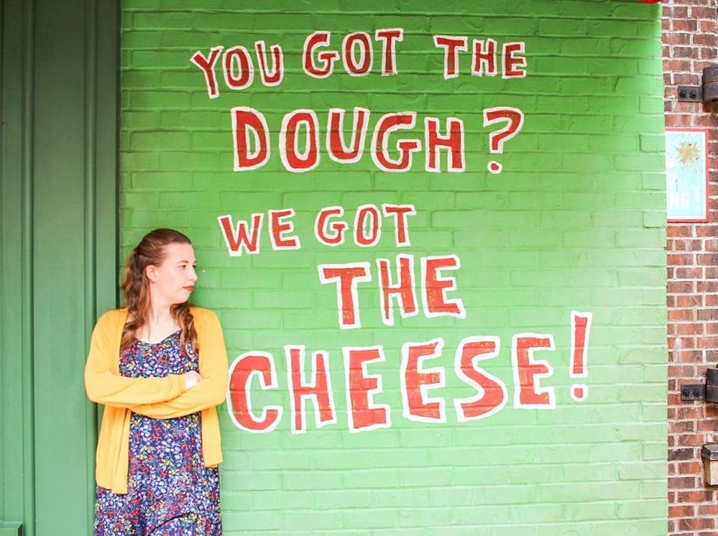 """A green wall with red letters outlined in white that reads """"You got the dough? We got the cheese!"""" in Disney's Hollywood Studios."""