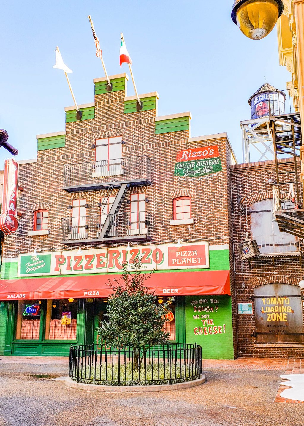 PizzeRizzo at Disney's Hollywood Studios. It is a fire escape, a green wall, and a tree in front.