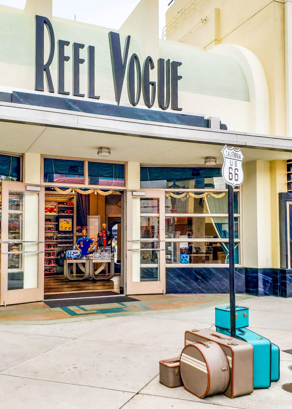 """A store with a sign that says """"Reel Vogue"""". In front of it is a sign for Route 66 and several suitcases."""