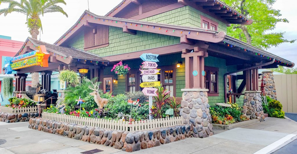 A side view of the Antiques and Curios Shop. A small house with green paneling and a brown sloped roof, with a neon sign that reads Hollywood Antiques and Curios. There is a raised stone wall and fenced lawn in front of it, with many various plans and lawn animals. It's one of the first buildings as you enter Disney's Hollywood Studios.