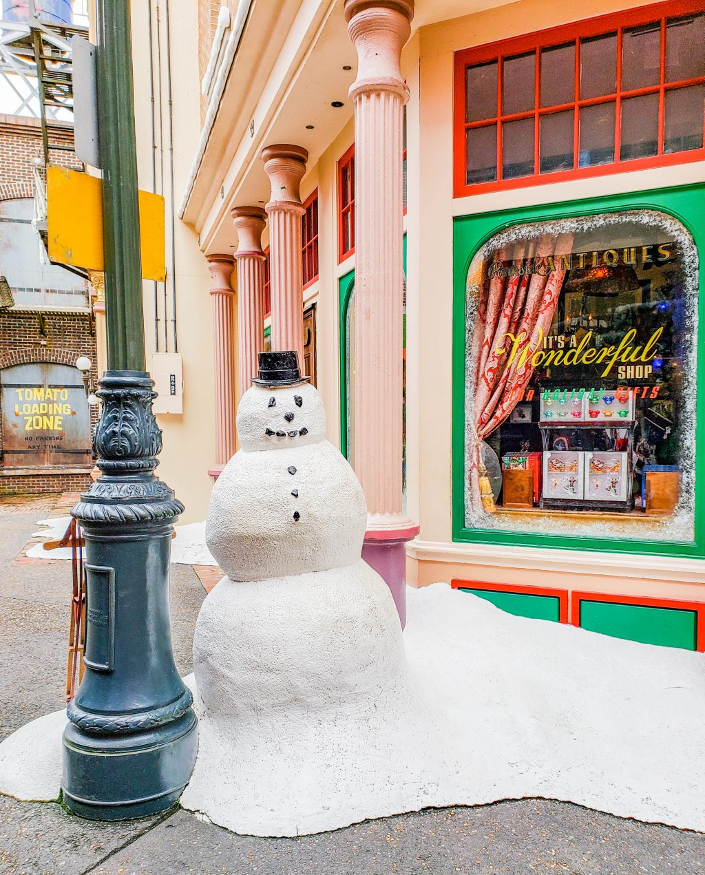 A snowman sits in front of a pile of snow in front of It's a Wonderful Shop in Disney's Hollywood Studios.