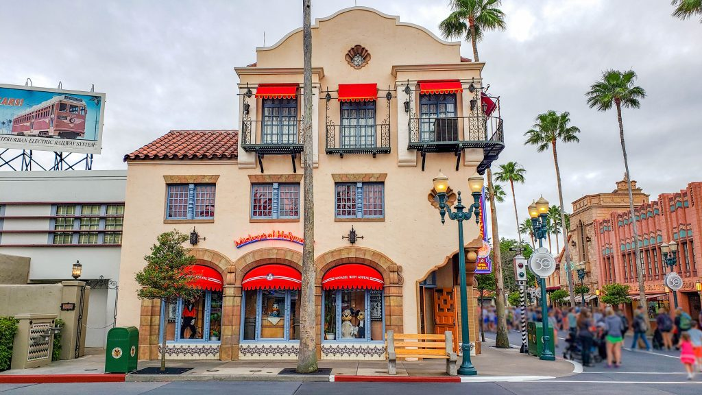 """A three-story stucco building with red awnings over the window. A neon sign reads """"Mickey's of Hollywood"""". To the right of the building you can see the other buildings along Hollywood Boulevard at Disney's Hollywood Studios."""