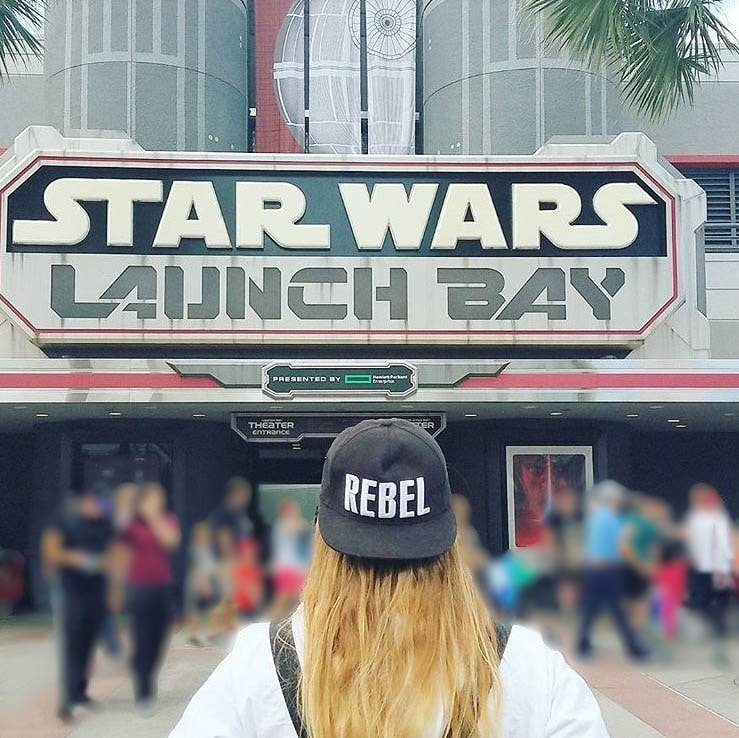 """Girl wearing """"Rebel"""" hat in front of Star Wars Launch Bay at Disney's Hollywood Studios"""